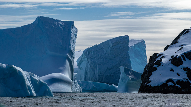 Jagged icebergs line up in interesting shapes, Antarctica.