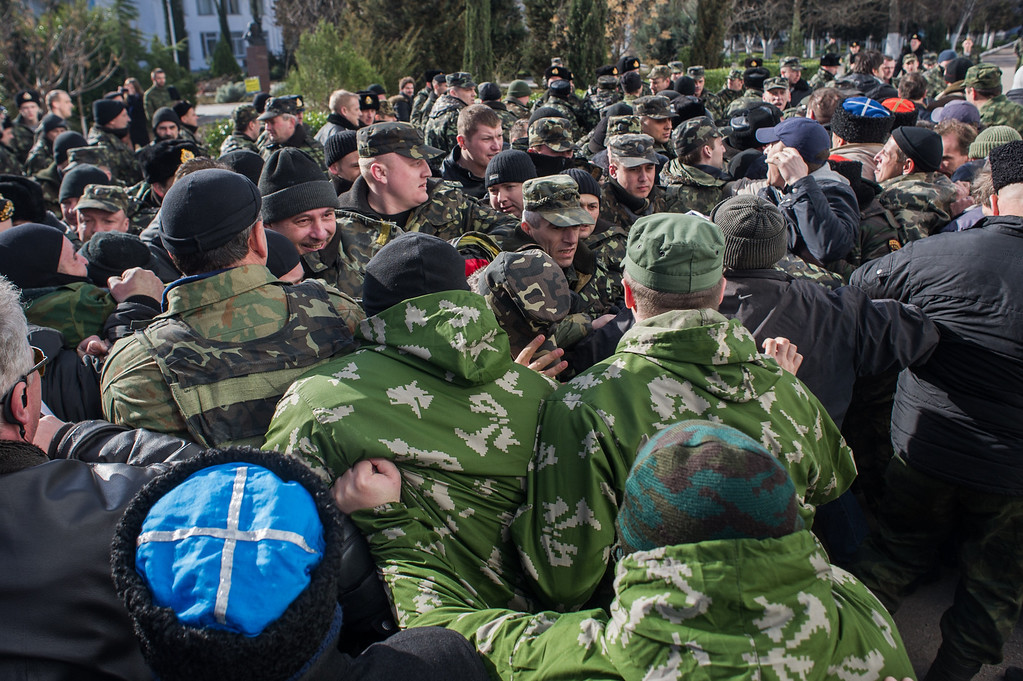 . Crimean self-defense forces scuffle with Ukrainian servicemen outside the Ukrainian Navy headquarters in Sevastopol, Crimea, Wednesday, March 19, 2014. (AP Photo/Andrew Lubimov)