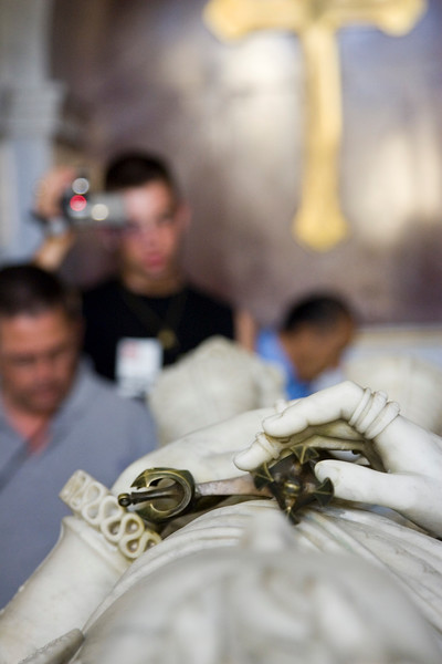 People visiting and recording the reclining statue of Don Juan de Austria (Don John de Austria) tomb at El Escorial Royal Pantheon, Spain. Don Juan de Austria (1547-1578) was the illegitimate half brother of the king Philip II. Selective focus on the statue's hands.