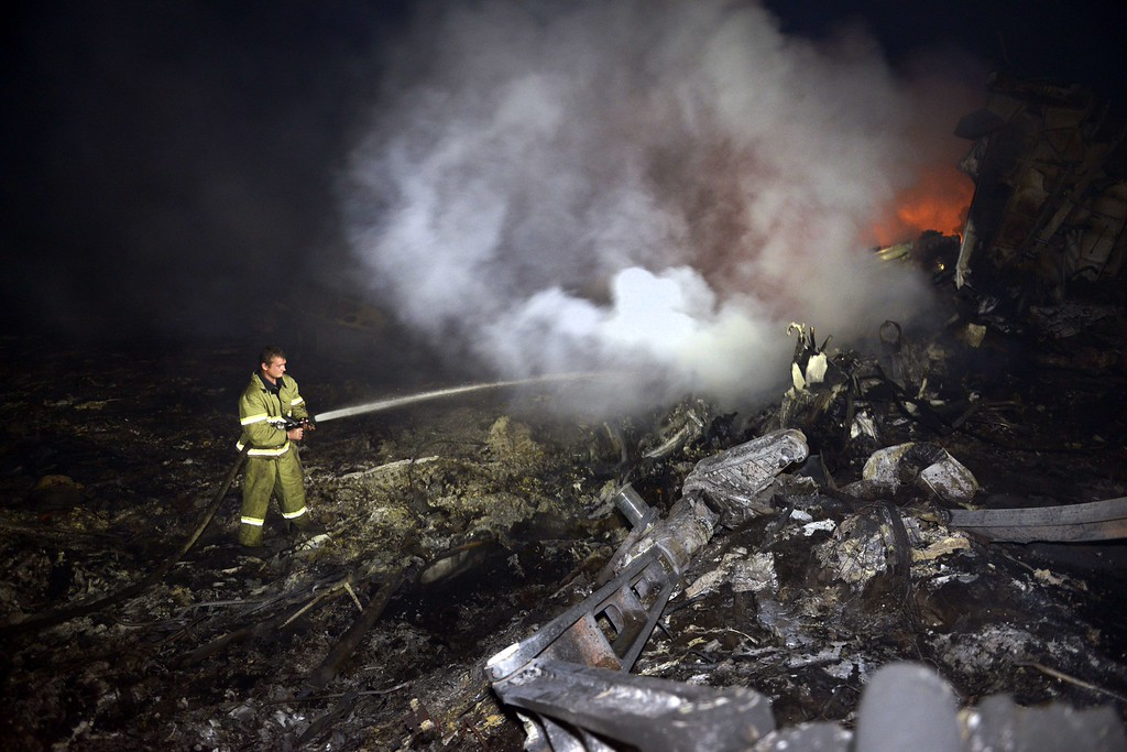 """. A firefighter sprays water to extinguish a fire, on July 17, 2014, amongst the wreckages of the malaysian airliner carrying 295 people from Amsterdam to Kuala Lumpur after it crashed, near the town of Shaktarsk, in rebel-held east Ukraine. Ukrainian President Petro Poroshenko said on Thursday that the Malaysia Airlines jet that crashed over rebel-held eastern Ukraine may have been shot down.\""""We do not exclude that the plane was shot down and confirm that the Ukraine Armed Forces did not fire at any targets in the sky,\"""" Poroshenko said in a statement posted on the president\'s website. AFP PHOTO/ ALEXANDER  KHUDOTEPLY/AFP/Getty Images"""