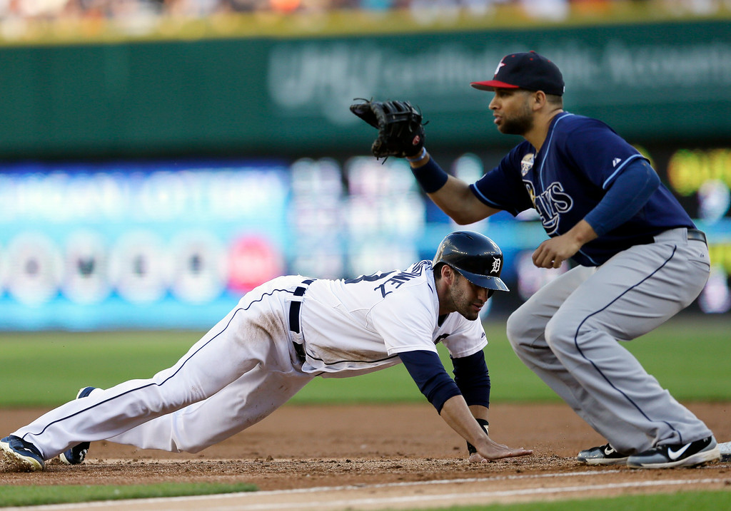 . Detroit Tigers\' J.D. Martinez, left, jumps safely back to first as Tampa Bay Rays first baseman James Loney awaits the pickoff throw during the second inning of a baseball game in Detroit, Friday, July 4, 2014. (AP Photo/Carlos Osorio)