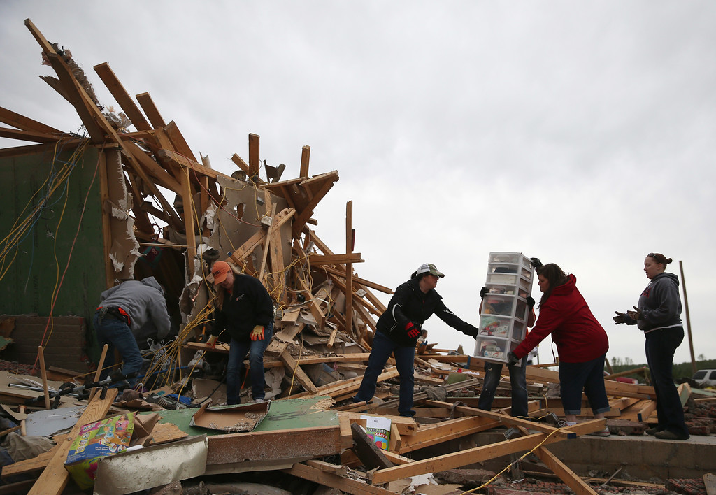 . Volunteers help clean debris at the site of a home that was detroyed when a tornado hit the area, April 29, 2014 in Vilonia, Arkansas. Deadly tornadoes ripped through the region April 27, leaving more than a dozen dead.  (Photo by Mark Wilson/Getty Images)