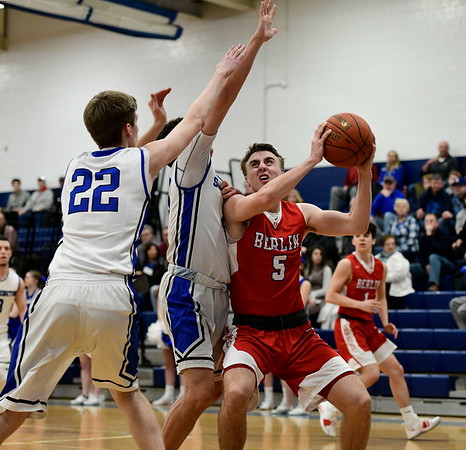 2/21/2019 Mike Orazzi | Staff Berlin High School's Ryan Hyde (5) and Southington's Jake Napoli (20) and Adam Hunter (22) during the CCC Boys Basketball Tournament in Southington Thursday night.