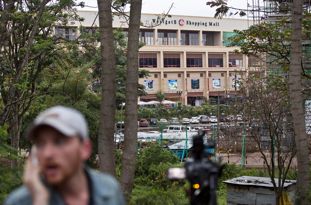 . A television reporter makes a telephone call while filming during a bout of heavy gunfire shortly after dawn, at the Westgate Mall in Nairobi, Kenya Tuesday, Sept. 24, 2013. Kenyan security forces battled al-Qaida-linked terrorists in an upscale mall for a fourth day Tuesday in what they said was a final push to rescue the last few hostages in a siege that has left at least 62 people dead. (AP Photo/Ben Curtis)