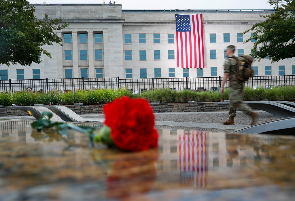 . A member of the military walks the grounds of the National 9/11 Pentagon Memorial before the start of the September 11th Pentagon Memorial Observance at the Pentagon on the 17th anniversary of the September 11th attacks, Tuesday, Sept. 11, 2018. (AP Photo/Pablo Martinez Monsivais)