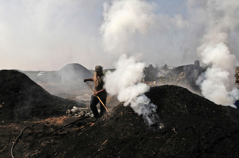 . A Palestinian worker covers the holes of smokes coming from a pile of smoldering wood during the process of turning wood into coal at one of the few local charcoal manufacturing shops, east of Gaza City on March 2, 2013. In adapting to years of border blockades and shortages, Gazans have become experts at recycling and making new out of old including turning scrap wood into charcoal to be used for barbecue grills and water pipes in local restaurants and coffee houses. (AP Photo/Hatem Moussa)