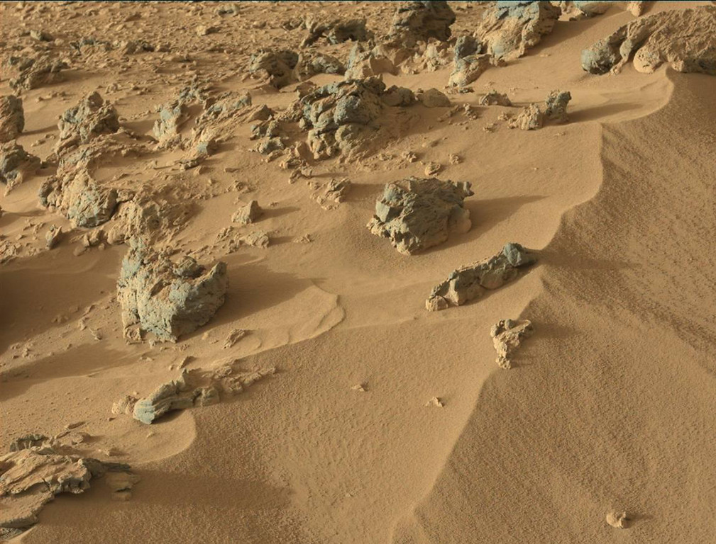 ". This October 30, 2012 image from the Mast Camera on NASA\'s Curiosity rover shows the upper portion of a wind-blown deposit dubbed ""Rocknest.\"" The rover team recently commanded Curiosity to take a scoop of soil from a region located out of frame, below this view. The soil was then analyzed with the Chemistry and Mineralogy instrument, or CheMin. The colors in the image are unmodified, showing the scene as it would appear on Mars, which has a dusty red-colored atmosphere. The rounded rock located at the upper center portion of the images is about 8 inches (0.2 meters) across.  NASA downplayed on November 21, 2012 talk of a major discovery by its Martian rover after remarks by the mission chief raised hopes it may have unearthed evidence life once existed on the Red Planet. Excitement is building over soon-to-be-released results from NASA\'s Curiosity rover, which is three months into a two-year mission to determine if Mars has ever been capable of supporting microbial life.  Its Sample Analysis at Mars (SAM) instruments have been sending back information as it hunts for compounds such as methane, as well as hydrogen, oxygen and nitrogen, that would mean life could once have existed there. = AFP PHOTO / NASA/JPL-Caltech/MSSS/"