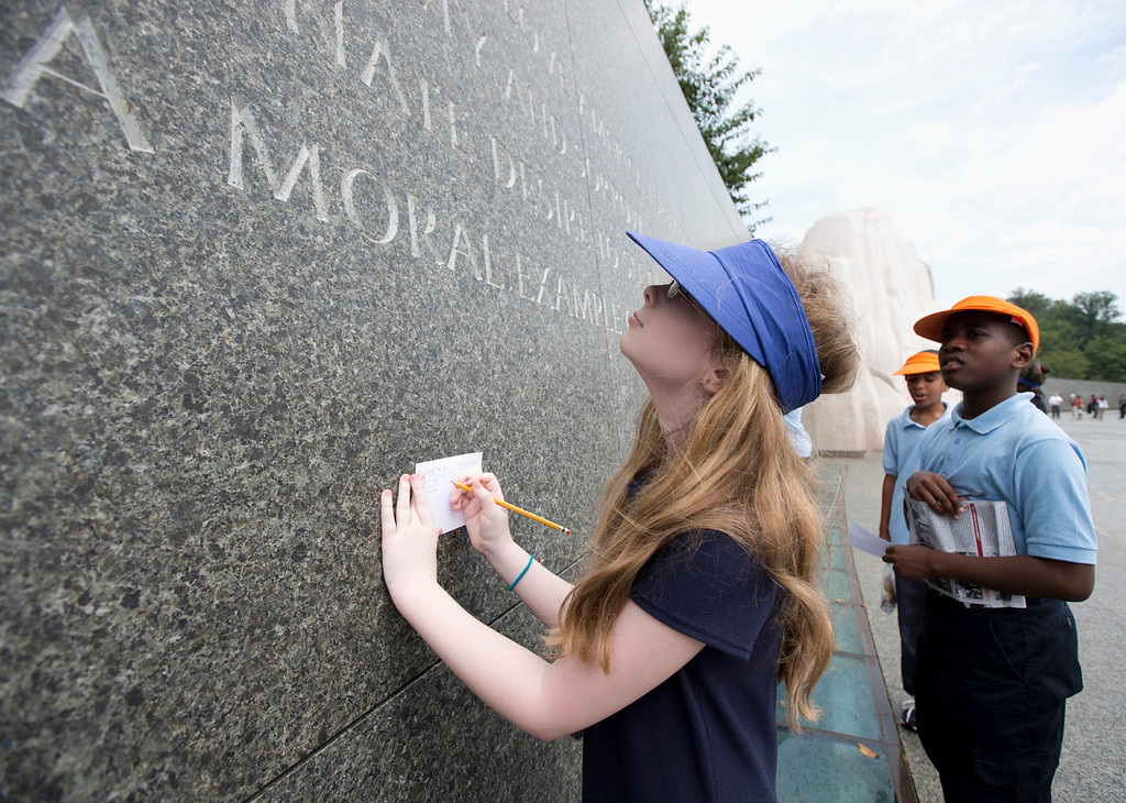 . Brianna Renner, 11, left, and Morgan Koroma, 11, both from Cora Rich Elementary School in Prince Georges County, Md., read and write down quotes from Martin Luther King\'s speeches and writings, inscribed on the wall at the Martin Luther King Memorial in Washington, Wednesday, Aug. 28, 2013, during the Let Freedom Ring ceremony commemorating the 50th Anniversary of the March on Washington for Jobs and Freedom. Renner, a sixth grader,  said that they are writing the quotes that they\'ll discuss in their Social Studies class, and pick which one they think is one that stands out most.    (AP Photo/Manuel Balce Ceneta)