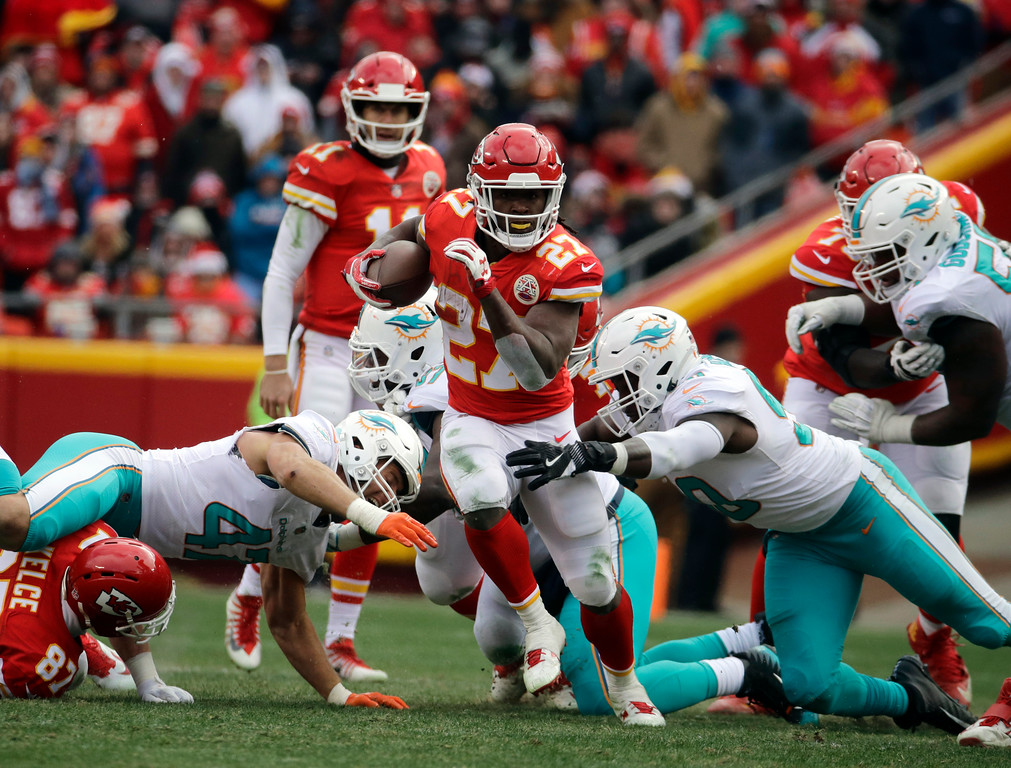 . Kansas City Chiefs running back Kareem Hunt (27) carries the ball away from tackle attempts by Miami Dolphins defensive end Charles Harris, right, and linebacker Kiko Alonso, left, during the first half of an NFL football game in Kansas City, Mo., Sunday, Dec. 24, 2017. (AP Photo/Charlie Riedel)