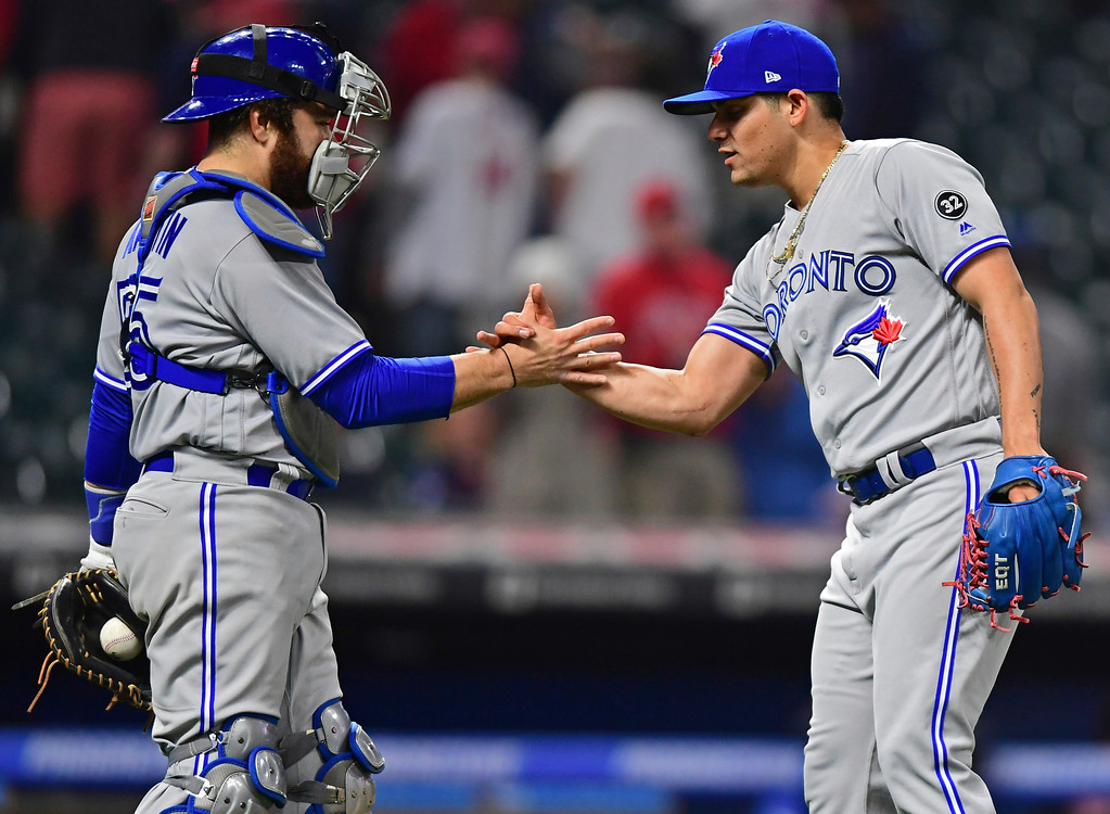 . Toronto Blue Jays relief pitcher Roberto Osuna, right, is congratulated by Russell Martin after the Blue Jays defeated the Cleveland Indians 8-4 in a baseball game Friday, April 13, 2018, in Cleveland. (AP Photo/David Dermer)