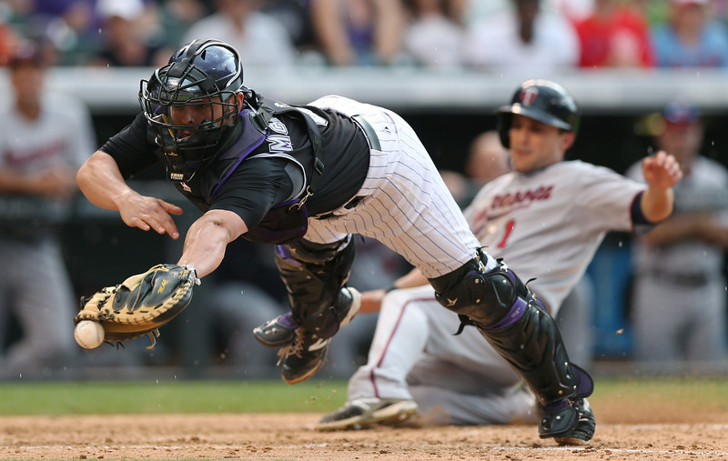 . Colorado Rockies catcher Michael McKenry, front, dives to field throw from outfield as Minnesota Twins\' Sam Fuld scores on a single by pinch-hitter Chris Parmelee in the eighth inning of the Twins\' 9-3 victory in an interleague baseball game in Denver on Saturday, July 12, 2014. (AP Photo/David Zalubowski)