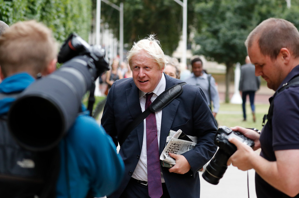 . British MP Boris Johnson walks near Whitehall in central London, Tuesday, Aug. 14, 2018 after roads were blocked when a car has crashed into barriers outside the Houses of Parliament. Authorities said in a statement Tuesday that a man in his 20s was arrested on suspicion of terrorist offenses after a silver Ford Fiesta collided with a number of cyclists and pedestrians before crashing into the barriers during the morning rush hour. (AP Photo/Frank Augstein)