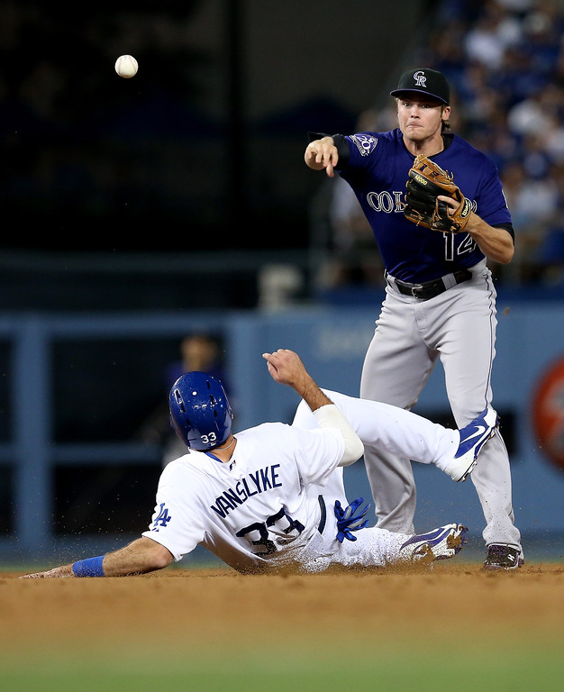 . Second baseman Josh Rutledge #14 of the Colorado Rockies throws to first after forcing out Scott Van Slyke #33 of the Los Angeles Dodgers to complete a double play ending a bases loaded threat in the seventh inning at Dodger Stadium on July 11, 2013 in Los Angeles, California.  (Photo by Stephen Dunn/Getty Images)