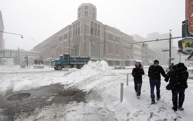 . Motorists and pedestrians go past a mound of snow that workers piled up in downtown Indianapolis, Wednesday, Dec. 26, 2012. (AP Photo/Darron Cummings)
