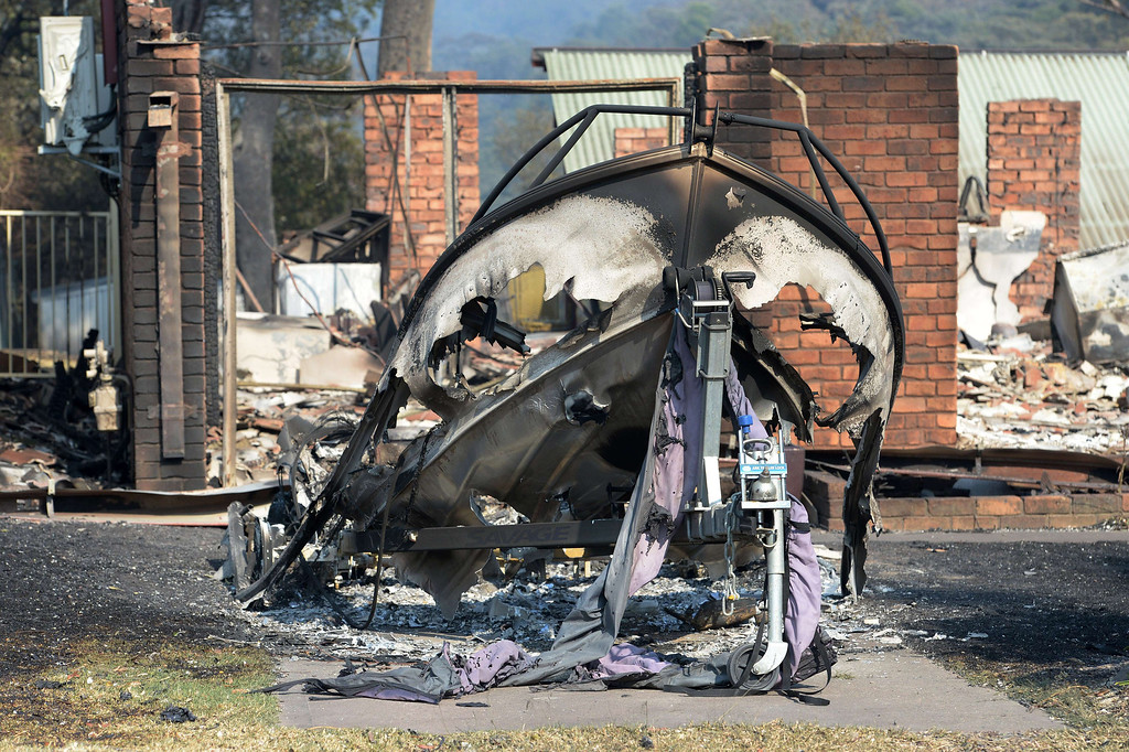 . A burnt out boat (C) sits in front of a house destroyed by bush fires in Winmalee in Sydney\'s Blue Mountains on October 18, 2013.  AFP PHOTO / Greg WOOD/AFP/Getty Images
