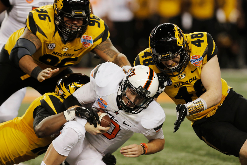 . Oklahoma State quarterback Clint Chelf (10) is tackled by Missouri safety Brock Bondurant (10) with help from linebacker Andrew Wilson (48), and defensive lineman Lucas Vincent (96) during the second half of the Cotton Bowl NCAA college football game on Friday, Jan. 3, 2014, in Arlington, Texas. (AP Photo/Brandon Wade)