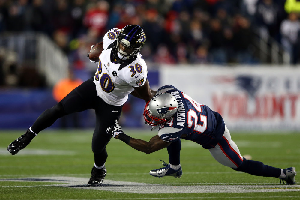 Description of . Bernard Pierce #30 of the Baltimore Ravens runs the ball against Kyle Arrington #24 of the New England Patriots during the 2013 AFC Championship game at Gillette Stadium on January 20, 2013 in Foxboro, Massachusetts.  (Photo by Elsa/Getty Images)