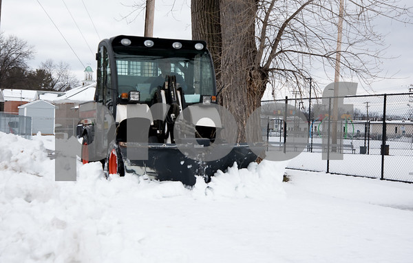 03/08/18 Wesley Bunnell | Staff A bobcat with a plow clears the sidewalk near Chesley Park on Thursday afternoon after a winter storm dumped heavy snow through the city on Wednesday afternoon and evening.
