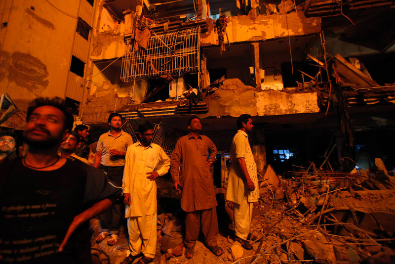 . Residents stand in front of a damaged building after a bomb blast in a residential area in Karachi March 3, 2013. A bomb attack in a Shi\'ite Muslim area of Pakistan\'s commercial capital Karachi killed 25 people and wounded 50 on Sunday, the police said. REUTERS/Akhtar Soomro