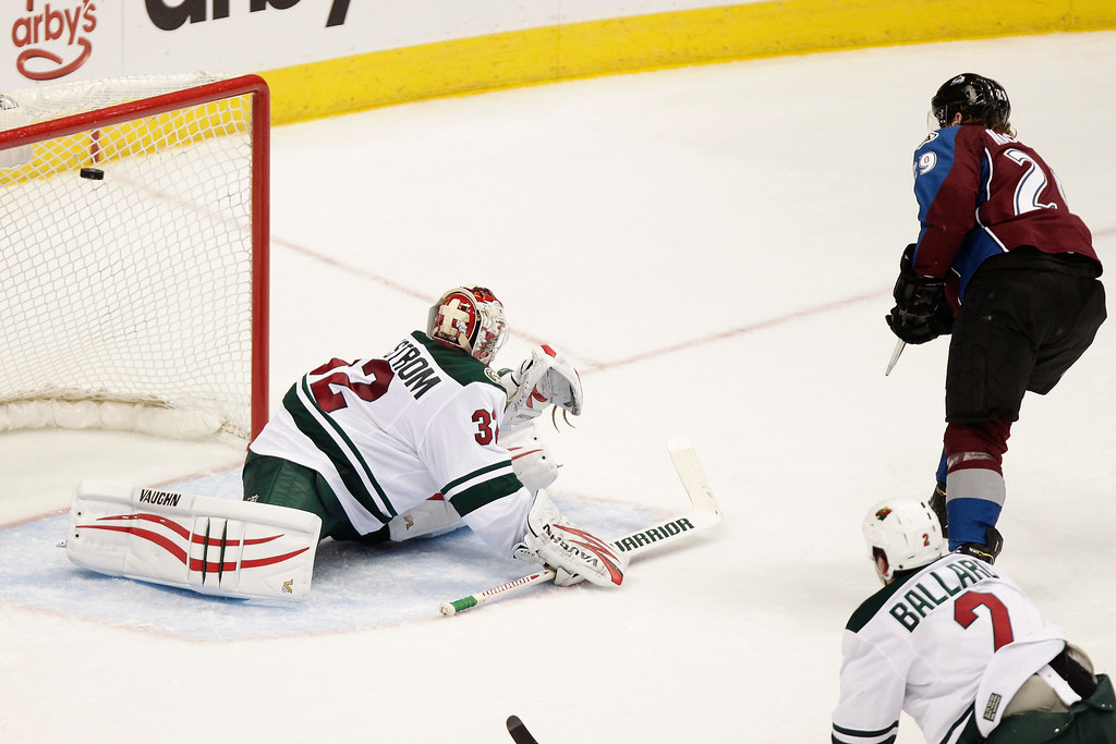 . Colorado Avalanche\'s Nathan MacKinnon (29) scores on Minnesota Wild goalie Niklas Backstrom (32), of Finland, during the third period of an NHL hockey game on Thursday, Jan. 30, 2014 in Denver. The Avalanche won 5-4. (AP Photo/Barry Gutierrez)