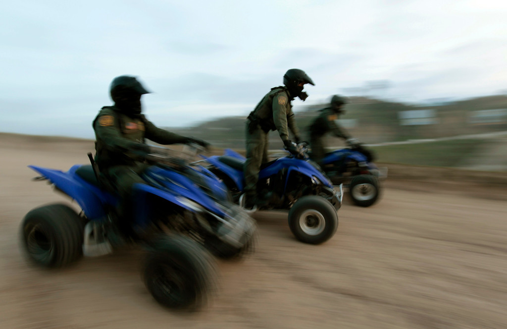 . U.S. Customs and Border Patrol agents Jarrod Yackel, Manny Villalobos, and David Faatoalia patrol on ATVs at dusk along the international border between Mexico and the United States near San Diego, California, March 26, 2013. Picture taken March 26, 2013. REUTERS/Mike Blake