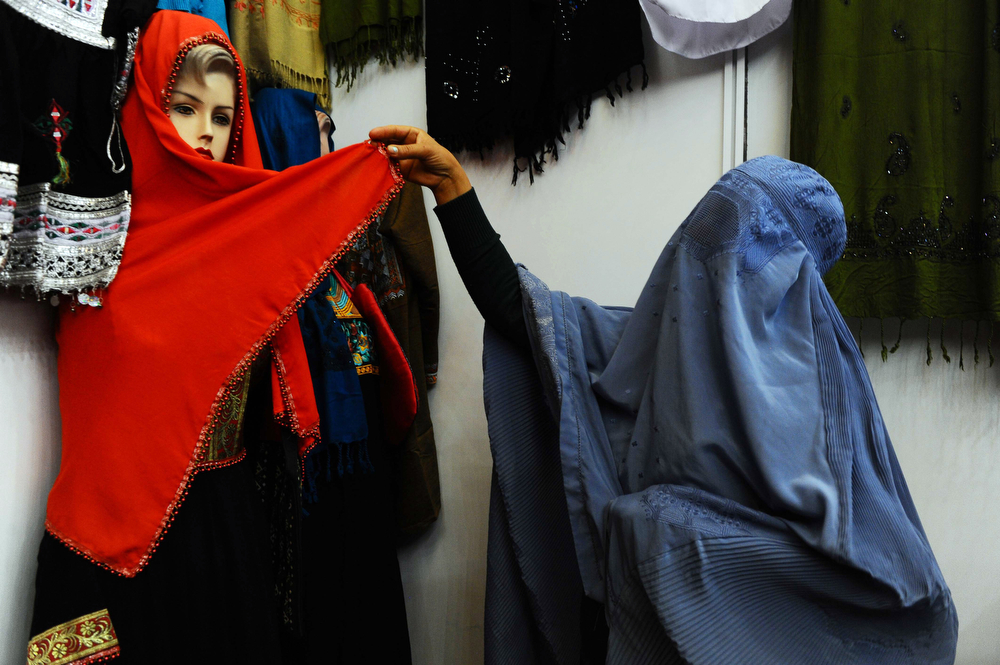 . A burqa-clad shopper looks at a headscarf at a women\'s handicraft exhibition to mark International Women\'s Day in Herat province on March 8, 2014. International Women\'s Day (IWD), originally called International Working Women\'s Day, is a global day observed annually on March 8, celebrating the economic, political and social achievements of women past, present and future. (Aref Karimi/AFP/Getty Images)