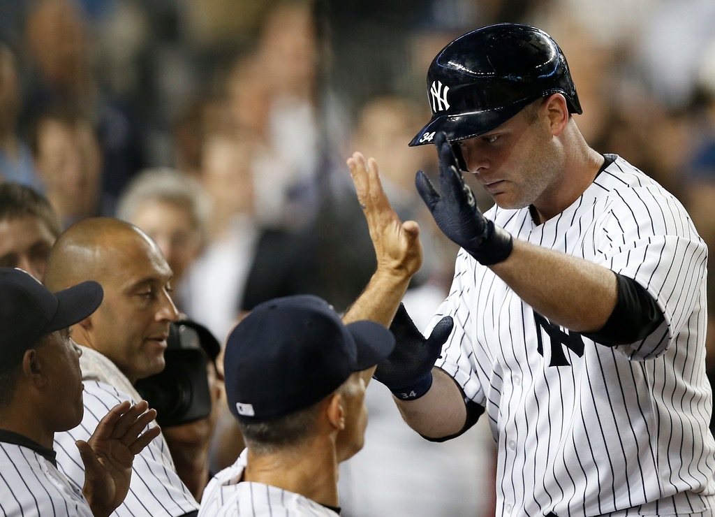 . New York Yankees Brian McCann, right, greets teammates after hitting a seventh-inning, go-ahead, solo home run off Detroit Tigers starting pitcher Justin Verlander in the Yankees 5-1 victory over the Tigers in a baseball game at Yankee Stadium in New York, Wednesday, Aug. 6, 2014.  (AP Photo/Kathy Willens)