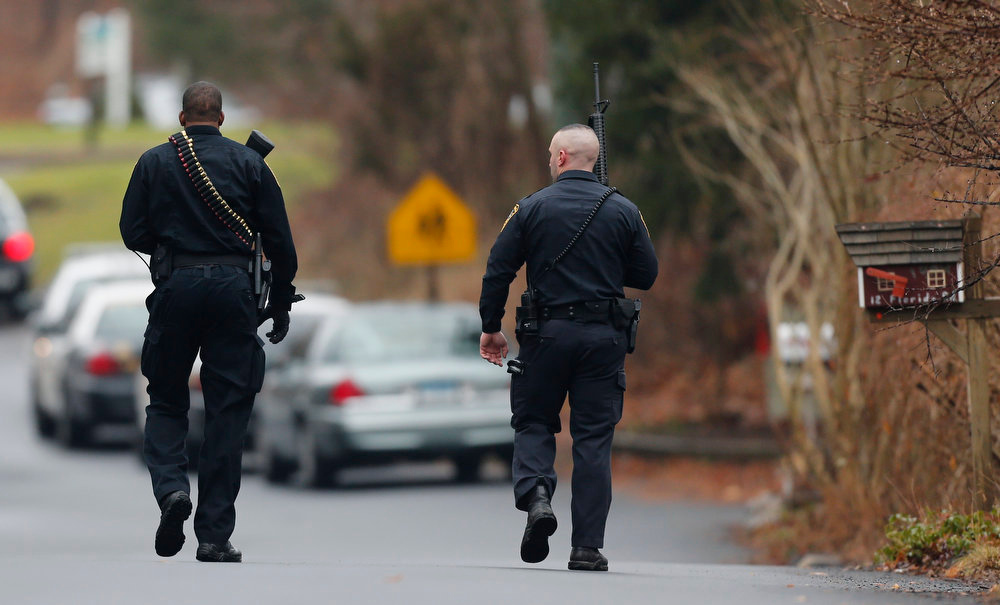 . Police officers walk up to an elementary school, which was in a lockdown, in Ridgefield, Conn., Monday, Dec. 17, 2012, after a suspicious person was seen near the train station close to the school. On Friday, authorities say a gunman killed his mother at their home and then opened fire inside the Sandy Hook Elementary School in Newtown, killing 26 people, including 20 children, before taking his own life. (AP Photo/Charles Krupa)