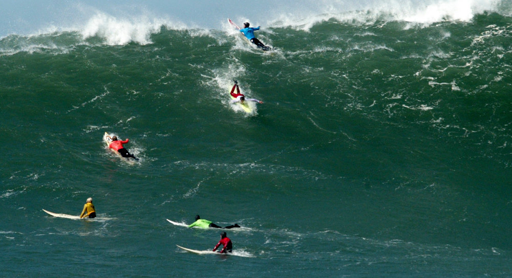 Description of . Competitors climb a mountain of water during the annual Mavericks Surf Contest on March 2, 2005.  The contest takes place in a legendary break in the Pacific Ocean one-half mile off the coast of Half Moon Bay, California .  Photograph by Shmuel Thaler/Santa Cruz Sentinel