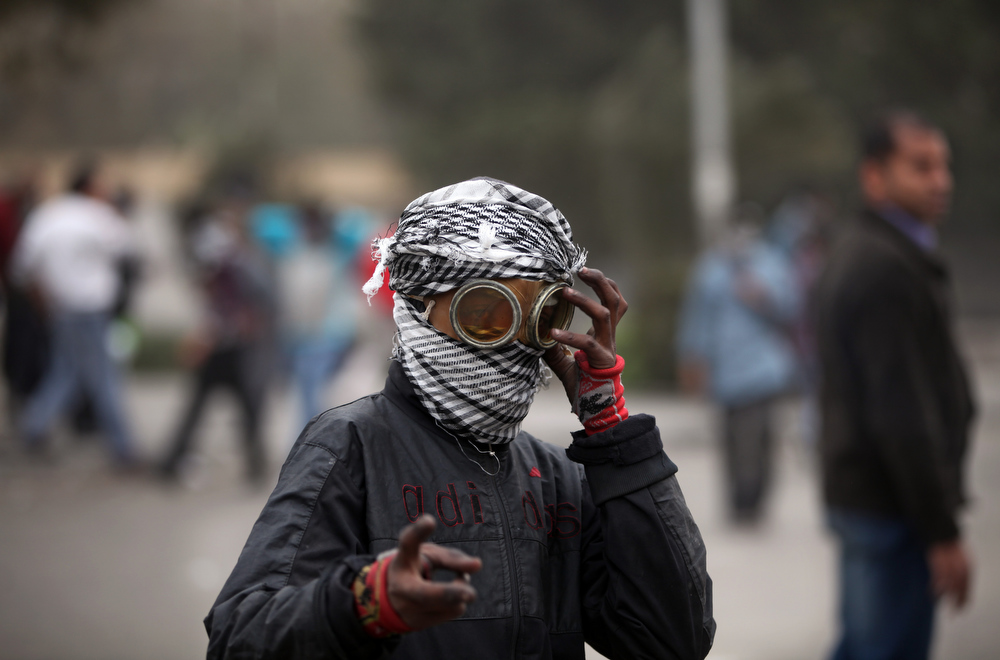 Description of . An Egyptian protester covers his face during clashes with riot police, not seen, near Tahrir Square, Cairo, Egypt, Monday, Jan. 28, 2013. Health and security officials say a protester has been killed in clashes between rock-throwing demonstrators and police near Tahrir Square in central Cairo. The officials say the protester died Monday on the way to the hospital after being shot. (AP Photo/Khalil Hamra)