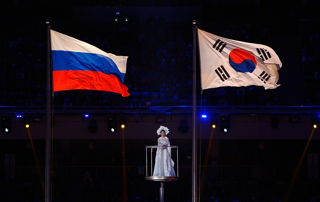 . The Russia and South Korea flags fly as a performer sings during the Sochi 2014 Paralympic Winter Games Closing Ceremony at Fisht Olympic Stadium on March 16, 2014 in Sochi, Russia.  (Photo by Dennis Grombkowski/Getty Images)