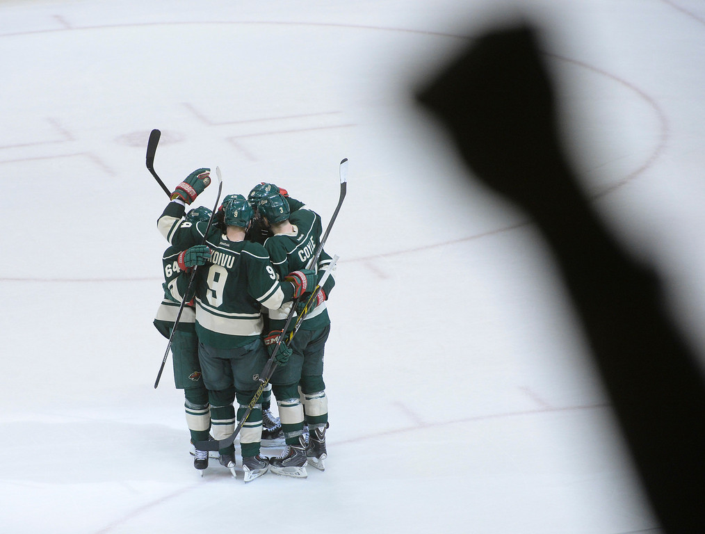 . Wild players celebrated the final empty net goal late in the third period.   (Photo by Karl Gehring/The Denver Post)