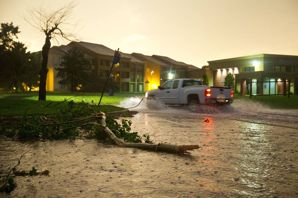 . A pickup truck drives through a flooded Highline Blvd just east of South Meridian Ave where several trees were also down after a tornado on  the ground near El Reno Okla. just south of Interstate 40 on Friday May 31, 2013. (AP Photo/The World-Herald, Chris Machian)
