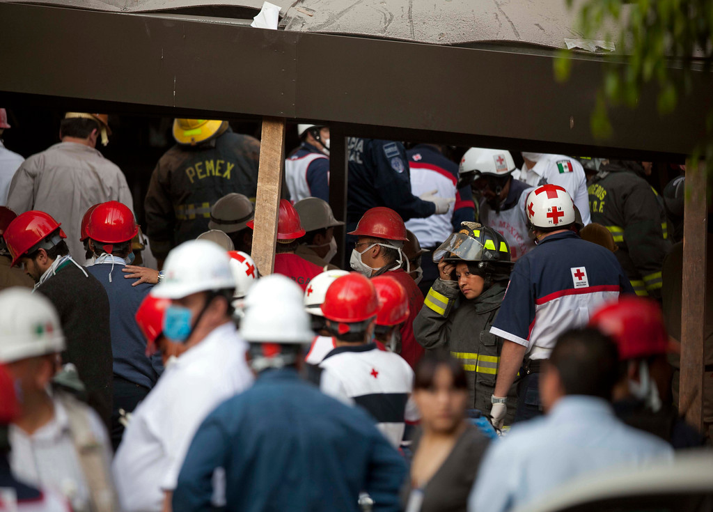 . Rescue workers and firefighters gather at the site of an explosion at an adjacent building to the executive tower of Mexico\'s state-owned oil company PEMEX, in Mexico City, Thursday Jan. 31, 2013.  (AP Photo/Eduardo Verdugo)