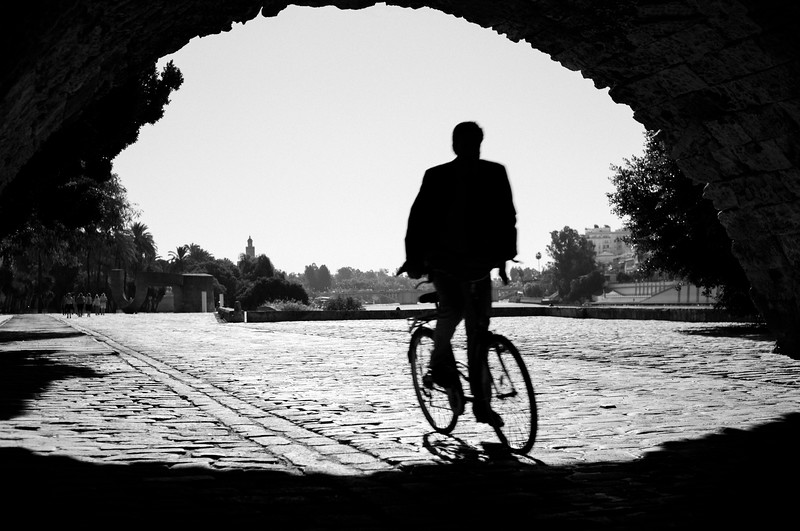 B&W picture of a cyclist riding under the Triana bridge, Seville, Spain