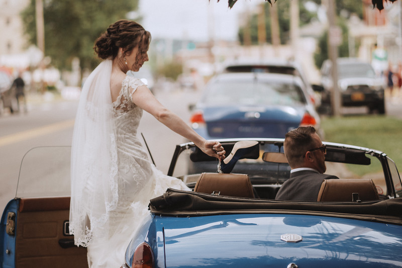 The bride throws her shoes into the back of a classic convertible as she gets into the driver seat next to the groom.