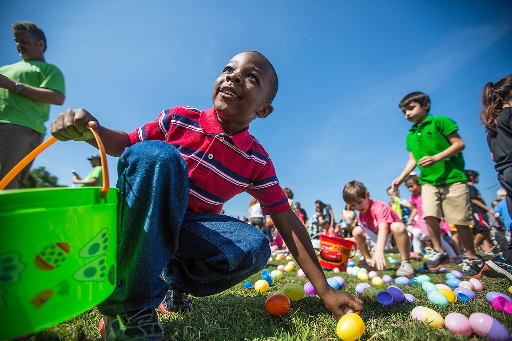 . Children race to pick up as many eggs as possible during Woodbridge Baptist Church\'s Easter Egg Scramble at Kingwood High School in Kingwood, Texas. (AP Photo/Conroe Courier, Andrew Buckley)