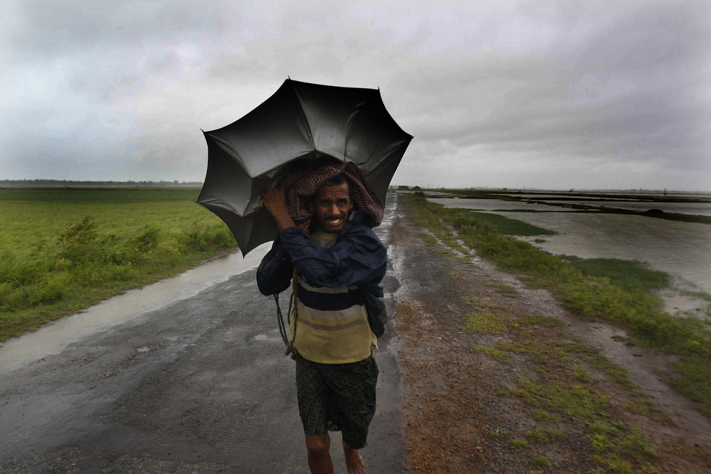. An Indian villager braving strong winds and rain walk to a safer place, in village Podampeta, in Ganjam district about 200 kilometers  (125 miles) from the eastern Indian city Bhubaneswar, India, Saturday, Oct. 12, 2013. Strong winds and heavy rains pounded India\'s eastern coastline Saturday, as hundreds of thousands of people took shelter from a massive, powerful Cyclone Phailin expected to reach land in a few hours. (AP Photo/Biswaranjan Rout)