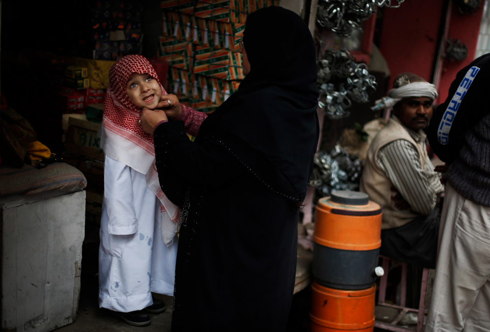 . An Indian Muslim woman dresses her child in traditional Arab dress during a procession to mark the birth anniversary of Prophet Muhammad in New Delhi, India, Tuesday, Jan. 14, 2014. (AP Photo/Altaf Qadri)