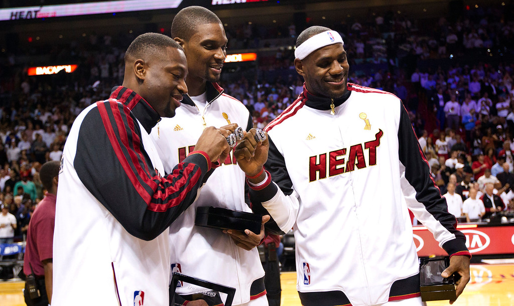 . From left, Miami Heat\'s Dwyane Wade, Chris Bosh and LeBron James pose with their 2012 NBA Finals championship rings during a ceremony before a basketball game against the Boston Celtics, Tuesday, Oct. 30, 2012, in Miami. (AP Photo/J Pat Carter)