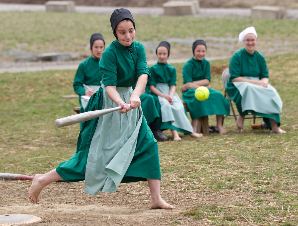 Description of . Amish girls play softball after class during an end of the school year celebration on Tuesday, April 9, 2013 in Bergholz, Ohio.  The celebration was also part of a farewell picnic for those sentenced in the hair and beard cutting scandal earlier in the year. (AP Photo/Scott R. Galvin)