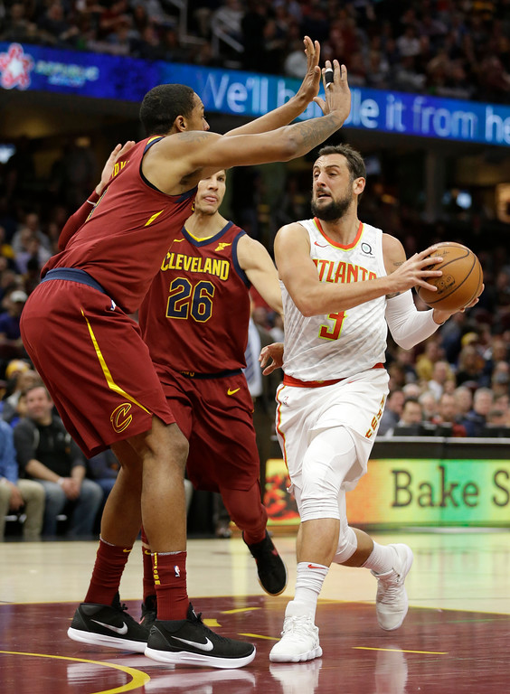 . Atlanta Hawks\' Marco Belinelli (3), from Italy, drives against Cleveland Cavaliers\' Channing Frye (8) and Kyle Korver (26) in the first half of an NBA basketball game, Tuesday, Dec. 12, 2017, in Cleveland. (AP Photo/Tony Dejak)