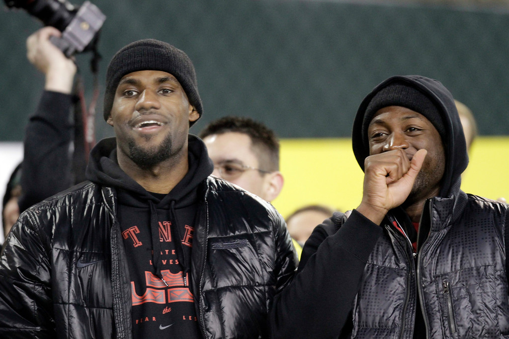 . Miami Heat players LeBron James, left, and Dwyane Wade share a laugh on the field before the NCAA college football game between Oregon and Southern California in Eugene, Ore., Saturday, Nov. 19, 2011. (AP Photo/Don Ryan)