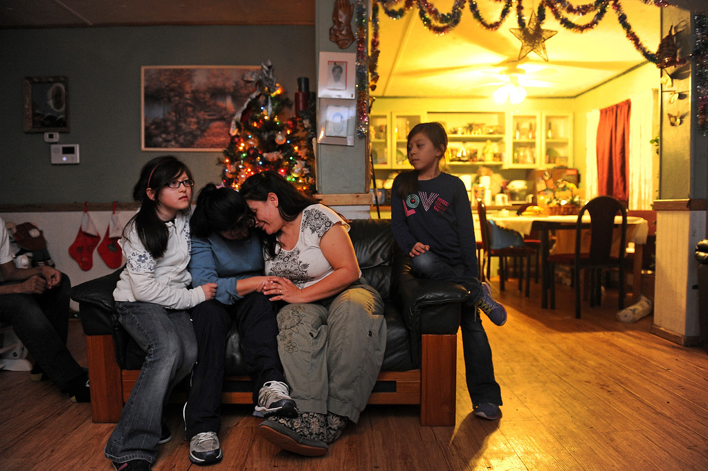. GREELEY, CO - DECEMBER 16, 2013:  Rosario Moreno gets comforted by her daughter Janeth, 10, left,and her  best friend Norma Meza, hug while sitting not the couch  after dinner in the living room Meza\'s tiny home in Greeley, CO on December 16, 2013. Moreno was sad because a loan she was hoping to receive to buy a new trailer didn\'t come through. (At right is Rosario\'s younger daughter Yanna, 8).  The Meza family, which consists of four children, Norma and her husband Martin have taken in the Moreno family after they lost everything in the September floods.  Rosario and her husband Jose have 5 children and are without a home at the moment.  Norma says she will help out her best friend for as long as she needs to.  The tiny house has 3 bedrooms and 2 small bathrooms and is home now to 14 people, 2 cats and 3 dogs.  (Photo By Helen H. Richardson/ The Denver Post)