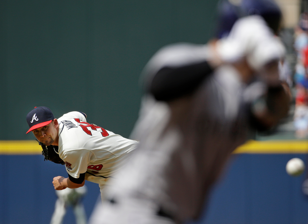 . Atlanta Braves starting pitcher Mike Minor, left, throws to Colorado Rockies\' Brandon Barnes in the first inning of a baseball game, Saturday, May 24, 2014, in Atlanta. (AP Photo/David Goldman)