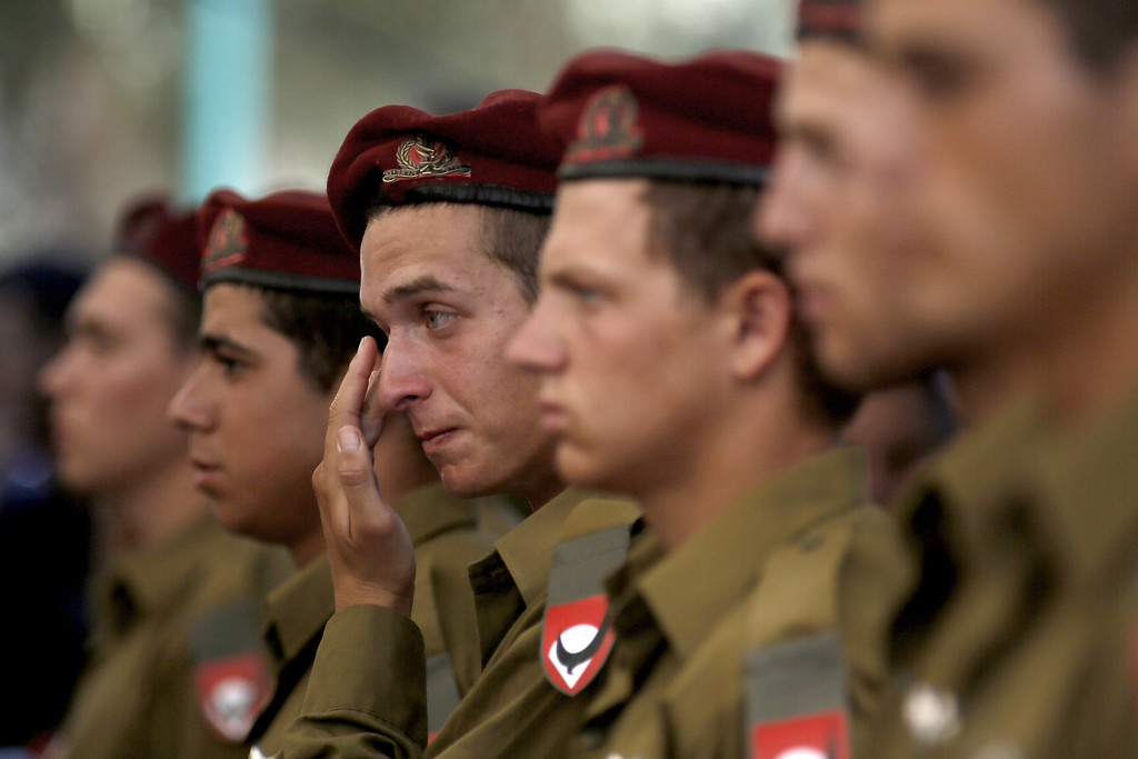 . Comrades of 20-year-old Israeli  St.-Sgt. Guy Algranati, mourn during his funeral in the military section of the Kiryat Shaul cemetery in Tel Aviv on July 31, 2014, after he was killed the previous day in combat in the Gaza Strip.  Israel said it would not pull troops from Gaza until they finish destroying a network of cross-border tunnels, and the army confirmed mobilising another 16,000 additional reservists, hiking the total number called up to 86,000. AFP PHOTO/ GALI TIBBON/AFP/Getty Images