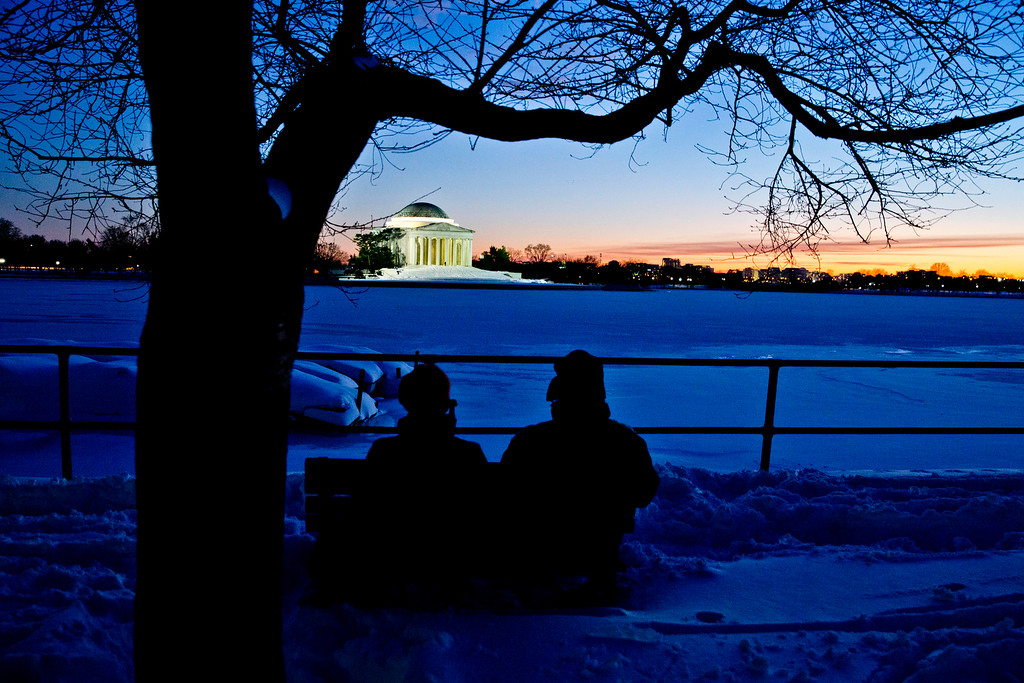 . Pirjo Garby, left, and Tom Henry, both of Washington, sit near the Tidal Basin and watch the sunset behind the Jefferson Memorial, Sunday, Jan. 24, 2016 in Washington. Brilliant sunshine and gently rising temperatures followed the mammoth blizzard that paralyzed Washington and set a single-day snowfall record in New York City, enabling millions to dig out Sunday and enjoy the winter. (AP Photo/Alex Brandon)
