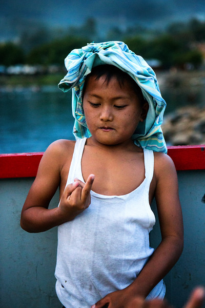 A young Batak boy practices his 'You Tube Signs' on a ferry across Lake Toba