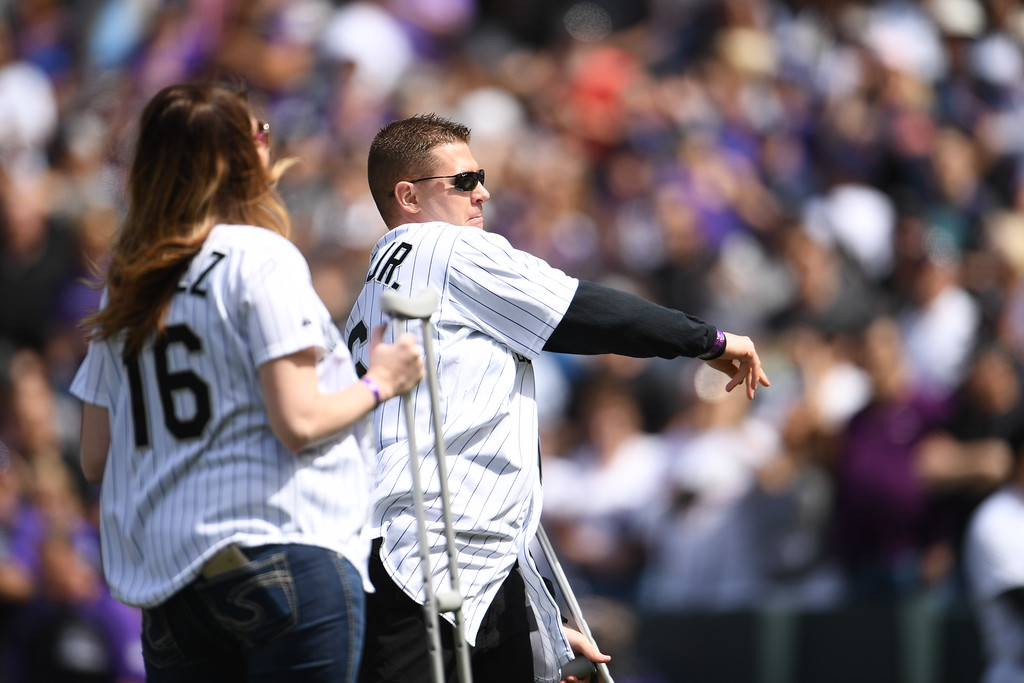. Wounded Denver police Sgt. Tony Lopez Jr. is accompanied by his wife Kristen as he throws out the first pitch. The Colorado Rockies played the San Diego Padres Friday, April 8, 2016 on opening day at Coors Field in Denver, Colorado. (Photo By RJ Sangosti/The Denver Post)