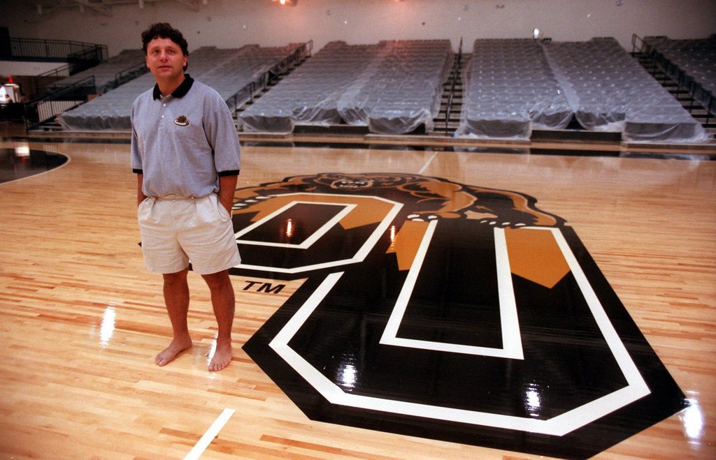 . Oakland University men\'s basketball head coach Greg Kampe at center court of the then-new basketball court at the Athletics Center O\'rena. The facility, which opened November 16, 1998, signified the school\'s ascension to Division I athletics.